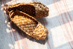Birch bark shoes, traditional old Russian shoes lie on an old traditional carpet in the sun. Shoes made from bark of tree.