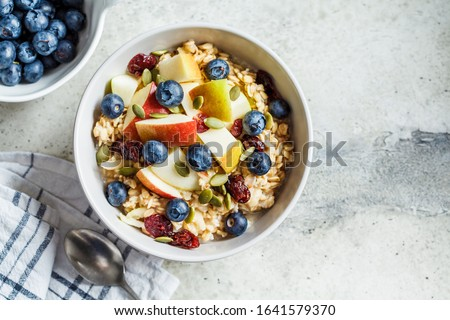 Bircher muesli or overnight oatmeal with apple, banana and blueberries in a gray bowl, copy space. Foto stock ©