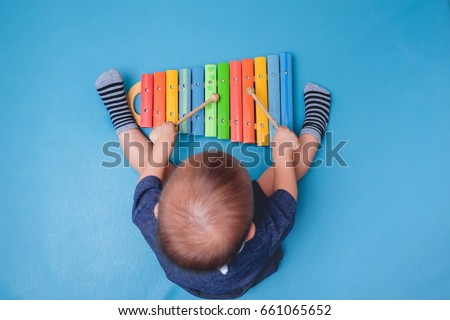 Bird eye view of Cute little Asian 18 months / 1 year old baby boy child hold sticks & plays a musical instrument colorful wooden toy xylophone, Educational toy for kids and toddlers concept
