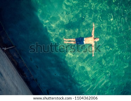 Bird eye view on the man floating in the pool, handsome guy with perfect stong body floating in transparent water, enjoying summer vacation
