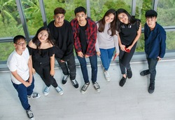 Bird-eye view portrait shot of group of seven young male and female teenagers standing and looking to the camera. College friends taking a photo together with cute smiling. Concept of relationship