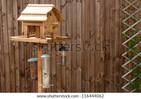 Bird Feeding Table with nuts and seeds hanging from it against a wooden fence with a trellis on it