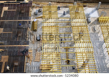 Bird's eye view at construction site where workers are preparing boards for ceiling