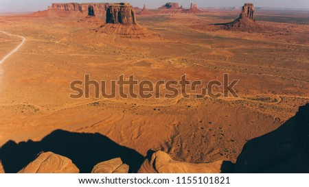 Bird's eye view of beautiful nature Monument Valley landmark of Arizona state. Aerial scenery view of wild lands at sunny day. High cliffs and endless sand desert #1155101821