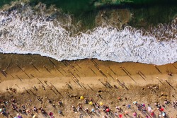 Bird's eye view of crowded beach with bathing people. People relaxing on the beach near ocean under umbrellas on sunny day. Aerial view of Playa Caleta Portales beach. Valparaiso, Chile.