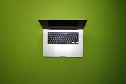 Bird's eye view of focus on a turquoise scroll wheel and a gray aluminum laptop with a large touchpad and black keyboard on a light green background.