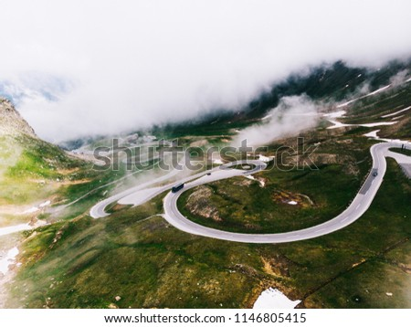 Bird's eye view of serpentine curves. Aerial view of scenic route in Austria with name Grossglockner High Alpine Road. Some of hairpin turns of Hochtor Pass. cloudy sky and snowy mountains