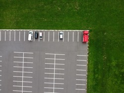 Bird's eye view of the red cars and green grass in the parking lot from above.