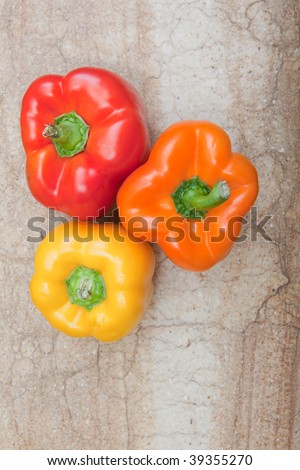 Bird's eye view of three bell peppers sitting on cutting board.