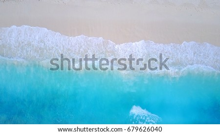 Bird's eye view of waves on white sand beach