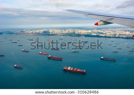 Bird\'s-eye view seascape with cargo ship in the morning from window of airplane with cityscape background.