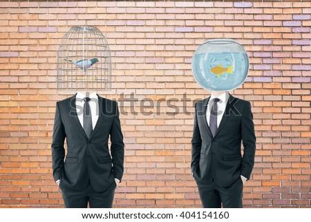 Birdcage and fishtank headed businessmen on brick background, 3D Rendering