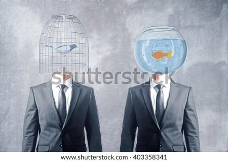 Birdcage and fishtank headed businessmen on concrete background