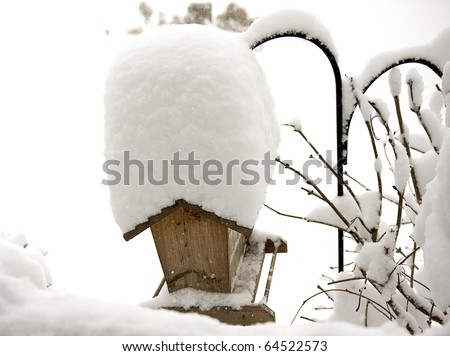 Birdhouse covered high with snow after severe winter storm - stock photo
