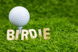 Birdie word with golf ball behind on green grass. Birdie: A score of one under par on a hole.