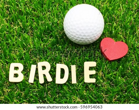 Birdie wording with golf ball and red heart are on green grass