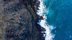 Birds Eye shot of pacific ocean hitting cliffs