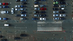 Birds eye view cars moving at mall parking place of shopping center. Drone footage people walking at large parking space. Copter filming parking lot with people at city.