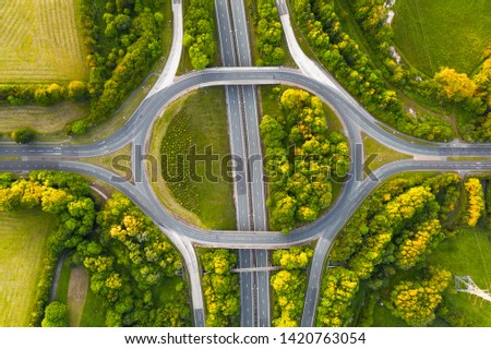 Birds eye view of a typical British highway intersection, shot on a very quiet evening during sunset with no traffic.  #1420763054