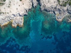 Birds eye view of transparent blue waters with coral reefs and cliffs on tropical island