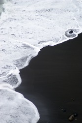 Birds eye view of white foamy surge at volcanic black sandy beach, coast of island Sao Miguel, Azores, Portugal