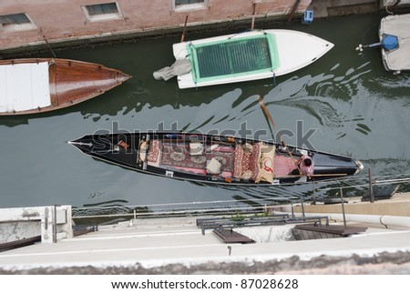 Birds eye view on gondola in narrow canal, venice, Italy, Europe. Boats are the daily traffic in this famous city. Watch out for the shape the paddle creates in the water #87028628
