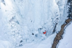 Birds eye view shot of a Caucasian male athlete climbing down the side of an icy slope, using rope attached to his harness