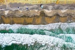 Birdseye drone POV of heavy waves in San Diego at Torrey Pines beach with cliffs