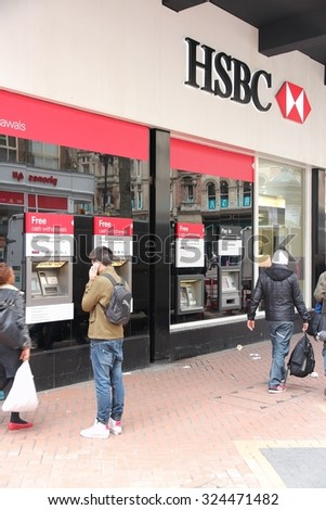 BIRMINGHAM, UK - APRIL 19, 2013: People walk by HSBC Bank in Birmingham, UK. HSBC is one of largest bank groups, holding assets of $2.69 trillion worldwide (2012).