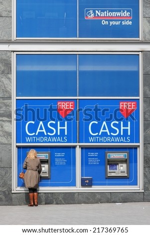 BIRMINGHAM, UK - APRIL 19, 2013: Person withdraws cash in Nationwide ATM in Birmingham, UK. Nationwide Building Society Group has 193.3 billion GBP in assets (2013).