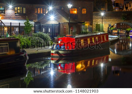 BIRMINGHAM, WEST MIDLANDS, UK - JUNE 25, 2017: A waterside view at night along the Birmingham Canal Navigations, where modern apartments overlook historic waterways, all making for a unique city area.