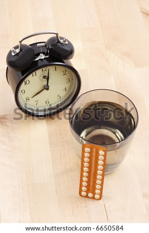 birth control pills alarm clock and glass of water