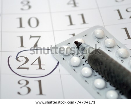 Birth control pills and pen closeup