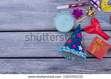 Birthday accessories on wooden background. Party hat, gift box, balloon, blowers and bows on wooden boards with text space.