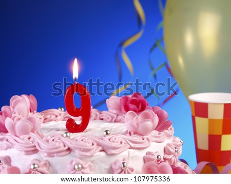 Birthday-anniversary cake with red candles showing Nr. 9
