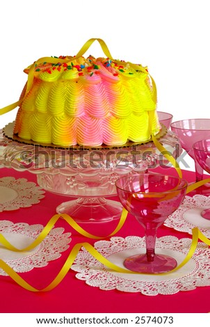 Birthday Cake - A pink and yellow iced birthday cake on a table decorated with yellow ribbons, pink stemware and white lace doilies