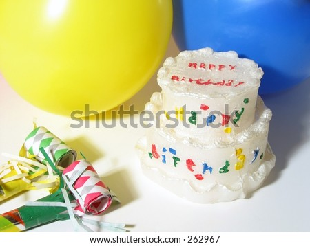 Birthday cake, balloons and party blowers