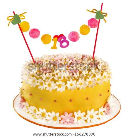 Birthday cake celebrating eighteen years, covering of flowers and daisies. Anniversary or birthday