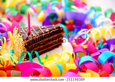 Birthday cake. Closeup top view of a piece of chocolate cake with a birthday candle decorated with confetti isolated in white background