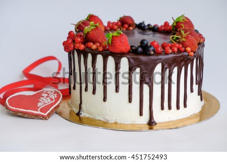 birthday cake decorated by chocolate and berry, strawberry on top near red gingerbread like heart shape and red ribbon on white background/different focus and angle