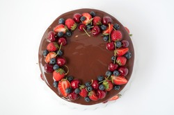 Birthday cake in chocolate with strawberries, blueberries and cherry on white background. Top view. Picture for a menu or a confectionery catalog.