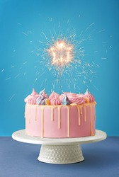 Birthday cake isolated on a blue background. Birthday party decorated cake with candles and sparkles. Copy space