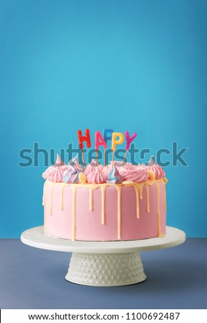 Birthday cake isolated on a blue background. Birthday party decorated cake with candles and sparkles. Copy space #1100692487