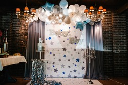 Birthday Cake on a background blue, white and silver balloons, brick wall. Baby shower party, decor. Cake with figure carriage for a boy. Copy space. Celebration baptism concept.