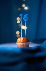 Birthday cake or muffin with number sixteen (16) and lights on the blue background. Birthday or anniversary concept