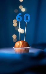 Birthday cake or muffin with sixty (60) number and blurred lights on the blue background. Birthday or anniversary concept
