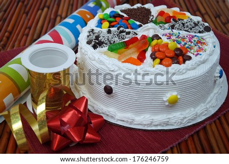 Birthday Cake, Ribbons and Bows.  A traditional birthday cake decorated with assorted candy next to party decorations wrapping paper, ribbon and a bow.