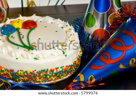 Birthday Cake with balloons on the icing and party hats on a table at a birthday party