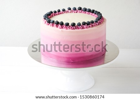 Birthday cake with blueberries and purple gradient cream on white background. Picture for a menu or a confectionery catalog.