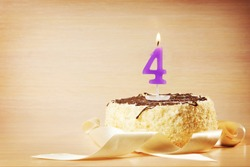 Birthday cake with burning candle as a number four. Focus on the candle